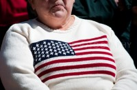 """A woman with an American Flag sweater in the crowd at the New Hampshire Tea Party Coalition's """"Tax Day' Rally at the State House in Concord, NH."""