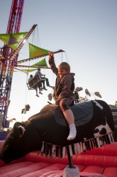 Logan Pierce, 7,  of Sanford rides a mechanical bull at the Rochester Fair in Rochester on Saturday.