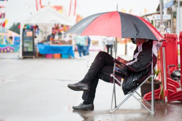 A concession attendant waits for customers on a rainy afternoon at the Rochester Fair on Tuesday
